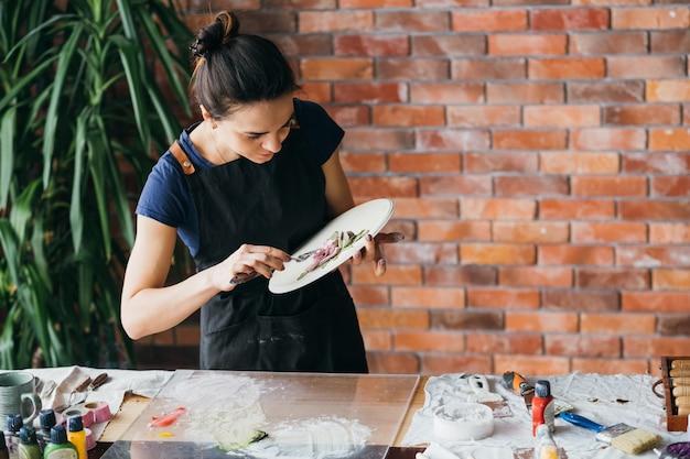 Sztuka gliny. rzemiosło ceramiczne. miejsce pracy w pracowni artysty. kobieta z narzędziami do modelowania tworzącymi grafikę kwiatową.