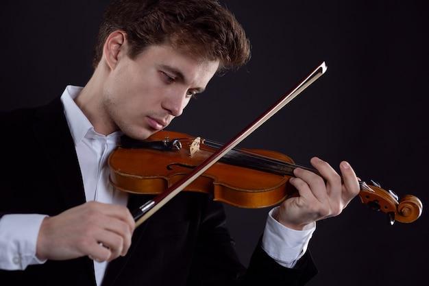 Sztuka i artysta. młody elegancki mężczyzna skrzypek skrzypek gra na skrzypcach na brązowym. muzyka klasyczna. strzał studio.
