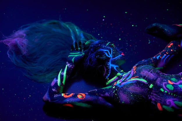 Sztuka kobieta body art na ciało tańczy w świetle ultrafioletowym. jasne abstrakcyjne rysunki na neonowym kolorze ciała dziewczyny. kobieta mody i sztuki, nieostra