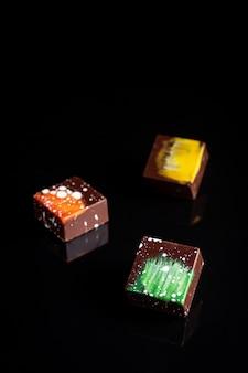 Sztuka kolorowe cukierki czekoladowe na czarny, wybrane fokus