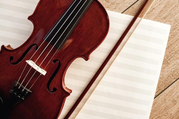 Sztuka komponowania. zamknij widok brązowy skrzypce z kokardą leżącą na arkuszach nut. lekcje skrzypiec. instrumenty muzyczne. sprzęt muzyczny.
