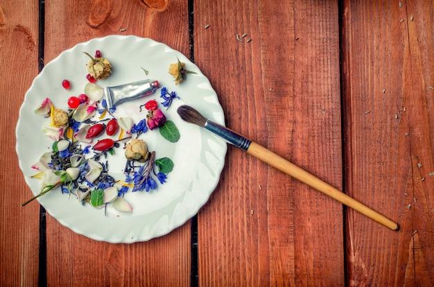 Sztuka konceptualna fotografia z kwiatami, pędzelkiem, tubką z farbą na talerzu na drewnianym tle