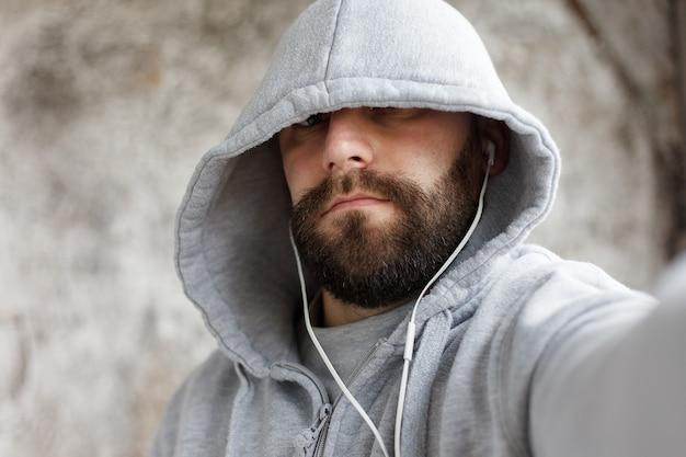 Sztuka, ludzie, emocje, muzyka, 4k i koncepcja stylu życia - model wypuszczony mężczyzna w studio stawia słuchawkę jak skała, elektronikę przy muzyce. młody przystojny brodaty mężczyzna słucha smartfona muzycznego w słuchawkach