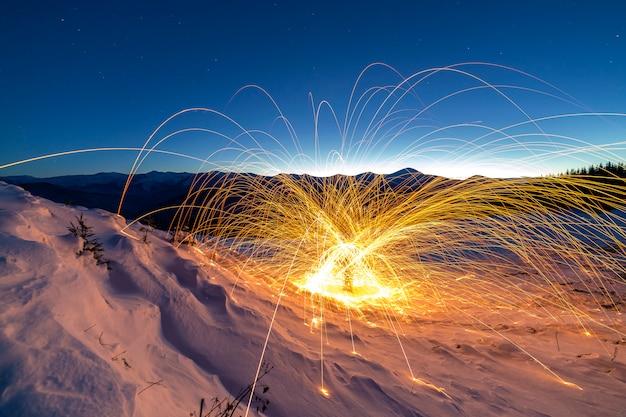 Sztuka malowania światłem. przędząca stalowa wełna w abstrakcyjnym okręgu, fajerwerkowe prysznice jasnożółtych świecących błyszczą w zimowej śnieżnej dolinie na grzbiecie górskim i niebieskiej nocy gwiaździstej przestrzeni kosmicznej.