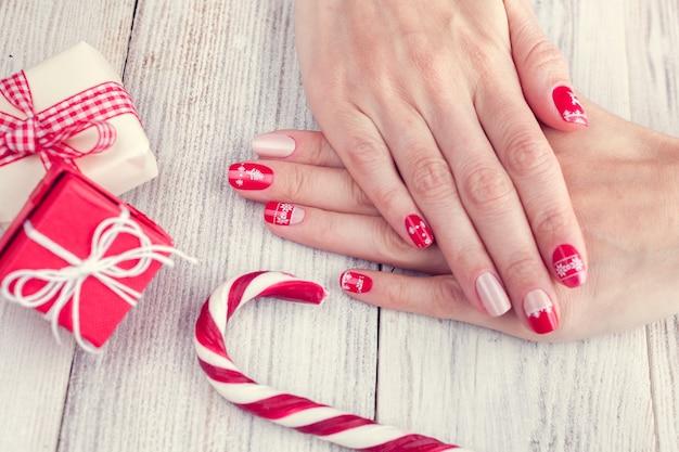 Sztuka manicure świąteczny na kobiece dłonie. obraz na białym drewnianym tle z prezentami i lizakiem