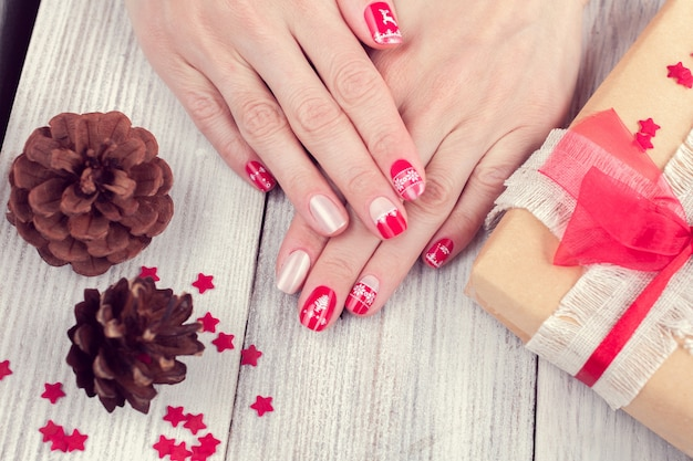 Sztuka manicure świąteczny na kobiece dłonie. obraz na białym drewnianym tle z prezentem i dwoma szyszkami
