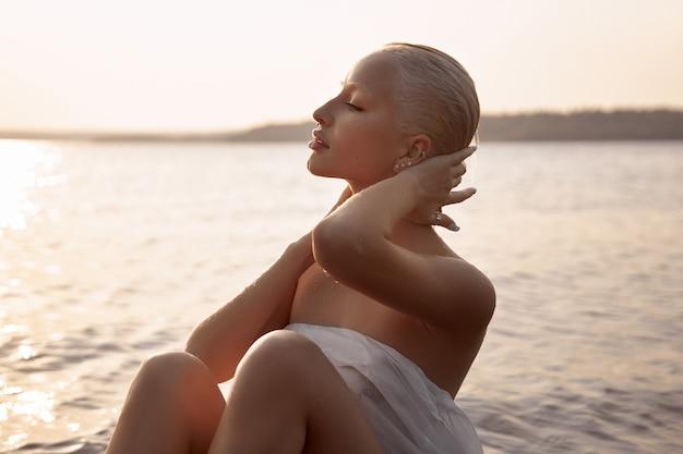 Sztuka nago seksowna blondynka z krótką fryzurą siedzi w wodzie na brzegu jeziora o zachodzie słońca. mokre włosy i ciało kobiety. ustronne wakacje na plaży?