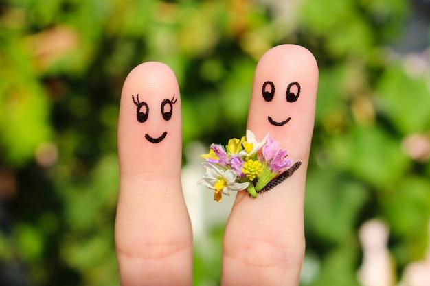 Sztuka palec szczęśliwej pary. mężczyzna daje kwiaty kobiecie.