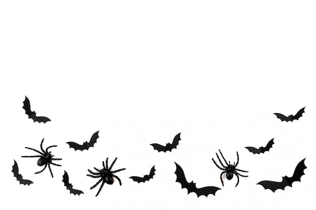 Sztuka papieru halloween. latające nietoperze z czarnego papieru i pająki na białym tle.