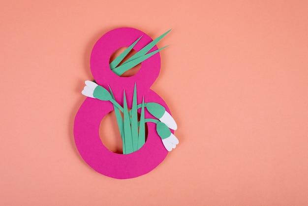 Sztuka papieru osiem numerów wyciętych w kolorze różowym na różowym tle z przebiśniegami wyciętymi z papieru. 8 marca, dzień kobiet tło z pustą przestrzenią.