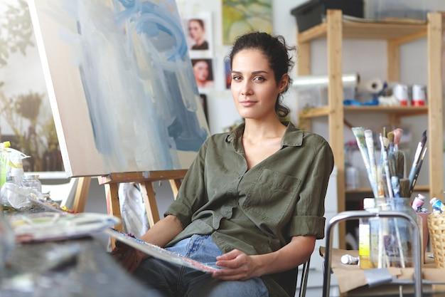 Sztuka, praca, inspiracja i kreatywność. portret pięknej, utalentowanej artystki brunetki w dżinsach i koszuli koloru khaki siedzącej w swoim warsztacie przed płótnem, pracującej nad malowaniem,