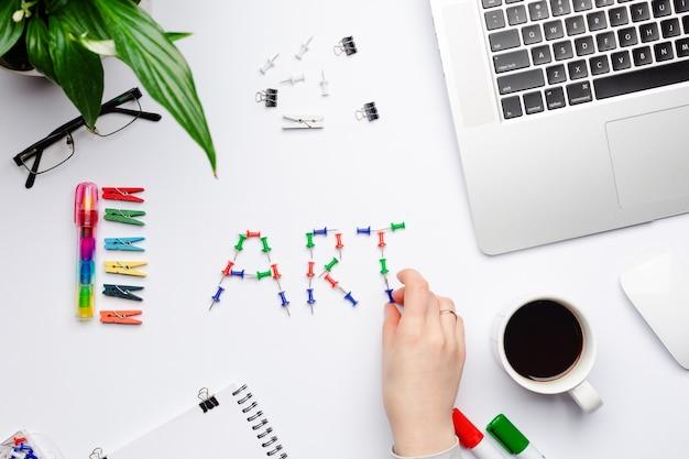 Sztuka słowna napisana kolorowymi szpilkami na stole roboczym z komputerem w miejscu pracy projektanta