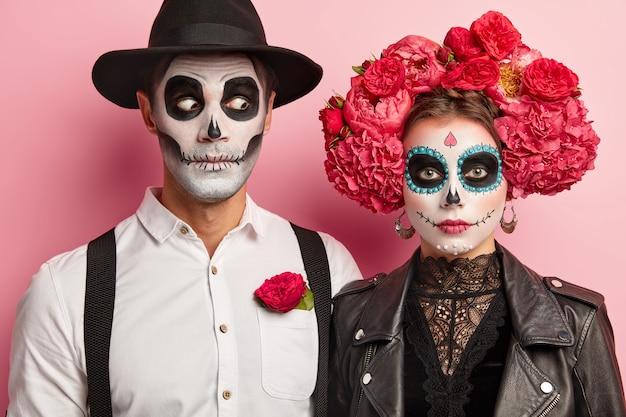 Sztuka twarzy halloween. kobieta i mężczyzna stoją razem w meksykańskim stroju