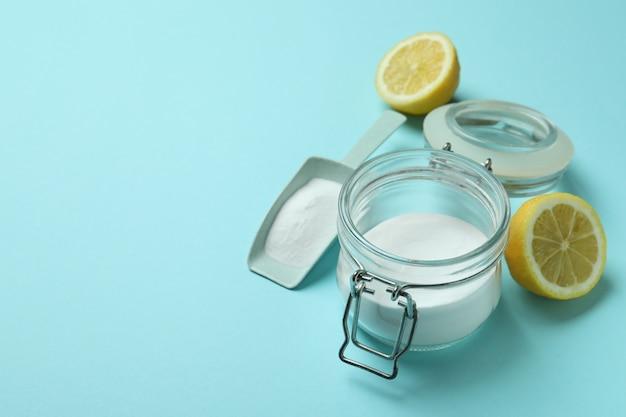 Szufelka i słoik z kwasem w proszku i połówki cytryny na niebieskim tle