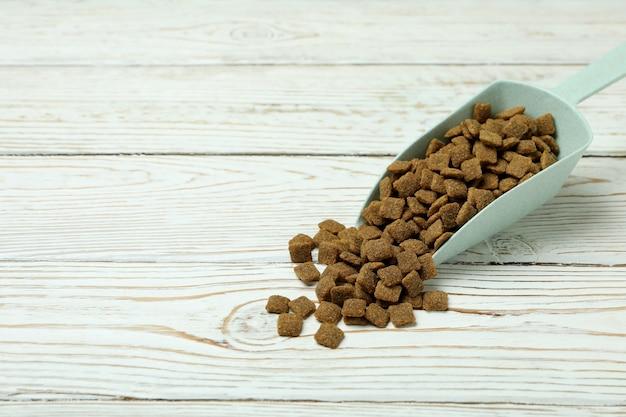 Szufelka z karmą dla zwierząt domowych na drewnianym