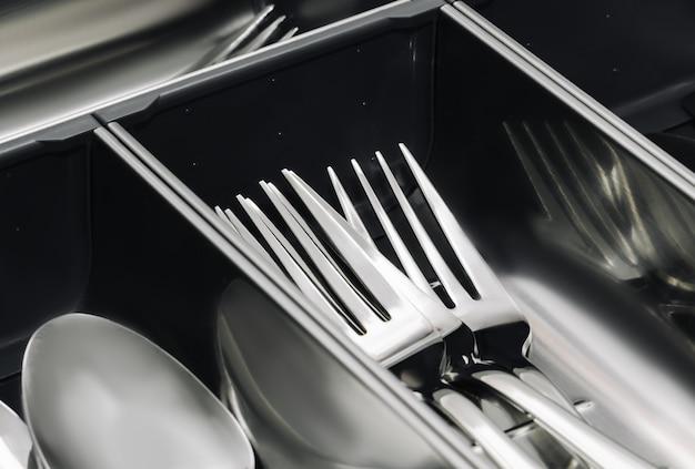 Szuflada na sztućce ze stali nierdzewnej z prostym zestawem narzędzi, łyżek i widelców. ścieśniać.