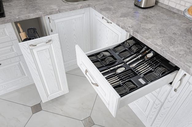 Szuflada ze srebrnymi sztućcami w nowoczesnej białej kuchni