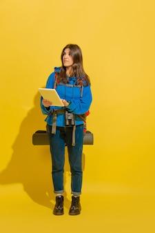 Szukam drogi z mapą. portret wesoły młody turysta kaukaski dziewczyna z torbą i lornetką na białym tle na żółtym tle studio. przygotowanie do podróży. ośrodek wypoczynkowy, ludzkie emocje, wakacje.