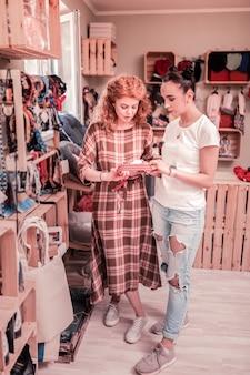 Szukam kołnierza. kręcona rudowłosa kobieta w kwadratowej sukience szuka obroży w sklepie zoologicznym