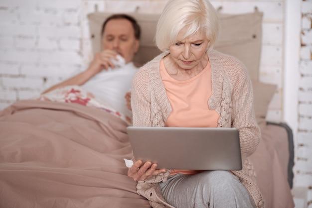 Szukam lekarza. starsza pani siedzi na łóżku przed chorym mężem i używa swojego nowoczesnego laptopa.