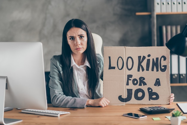 Szukam pracy. zdenerwowana sfrustrowana dziewczyna agent marketingowiec zwolniony firma koronawirus kwarantanna kryzys trzymać karton tekst siedzieć biurko stół nosić marynarka kurtka w miejscu pracy