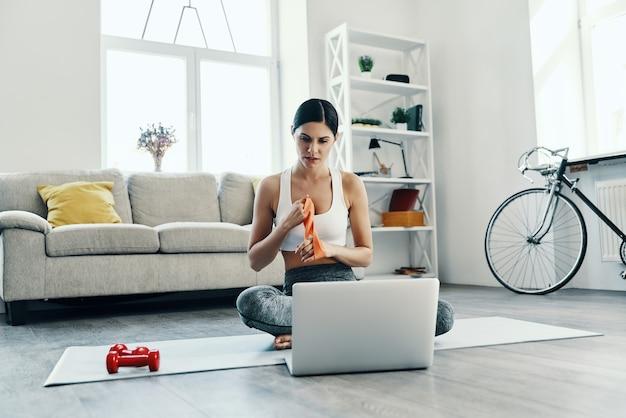 Szukanie, jak ćwiczyć. piękna młoda kobieta w sportowej odzieży przy użyciu laptopa podczas ćwiczeń w domu