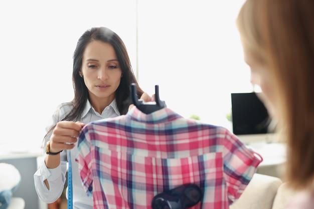 Szwaczki wykonujące pomiary koszulek centymetrową taśmą i prasowanie parowcem