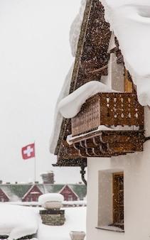 Szwajcarski domek podczas gęstego śniegu ze szwajcarską flagą w tle