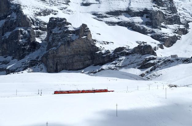 Szwajcarski pociąg górski przeszedł przez śnieg wysokogórski
