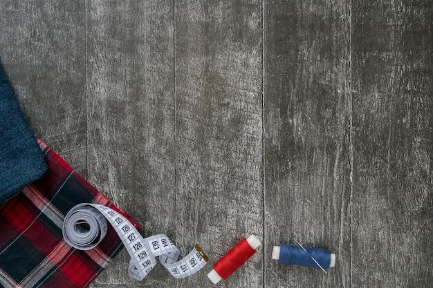 Szwalni akcesoria, cajgi i szkockiej kraty tkanina na ciemnym drewnianym tle.