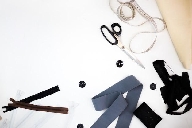 Szwalni akcesoria i tkanina na białym tle. nici do szycia, igły, szpilki, materiał, guziki i centymetr do szycia. widok z góry, płaski