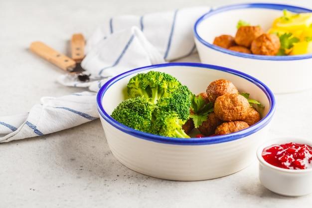 Szwedzkie klopsiki z brokułami, gotowanymi ziemniakami i sosem żurawinowym. koncepcja tradycyjnej szwedzkiej żywności.