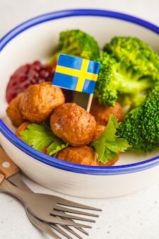 Szwedzkie klopsiki z brokułami i sosem żurawinowym. koncepcja tradycyjnej szwedzkiej żywności.
