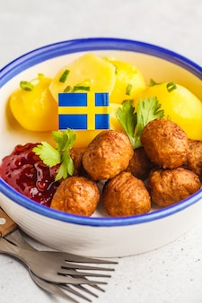Szwedzkie klopsiki z gotowanymi ziemniakami i sosem żurawinowym. koncepcja tradycyjnej szwedzkiej żywności.