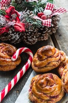Szwedzkie tradycje bożonarodzeniowe. bułeczki z rodzynkami szafran na podłoże drewniane z ozdób choinkowych, selektywny fokus. świąteczny nastrój. danie noworoczne