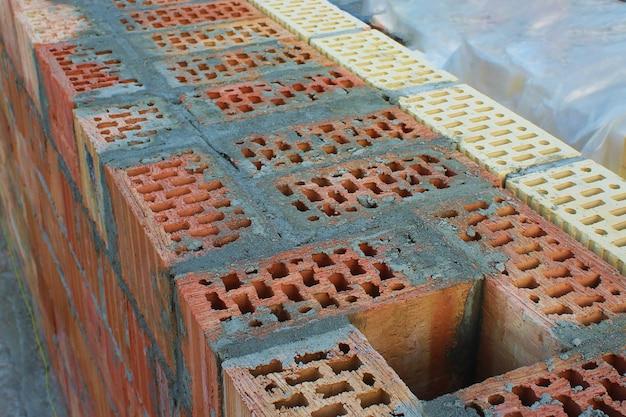 Szyb wydechowy w ścianie z czerwonej cegły wypełnionej cementem. okładziny z żółtymi i brązowymi cegłami. selektywne skupienie. koncepcja budowy. niedokończony dom jako symbol budownictwa.