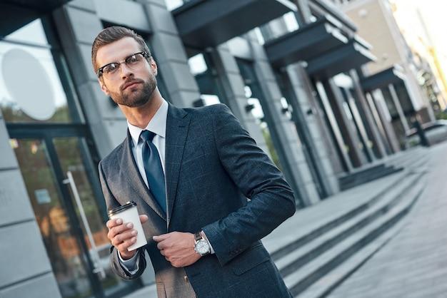 Szybka przerwa na kawę przystojny młody mężczyzna w pełnym garniturze i szkle