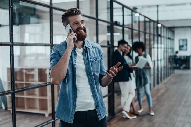 Szybka rozmowa biznesowa. przystojny młody uśmiechnięty mężczyzna rozmawia przez telefon i gestykuluje