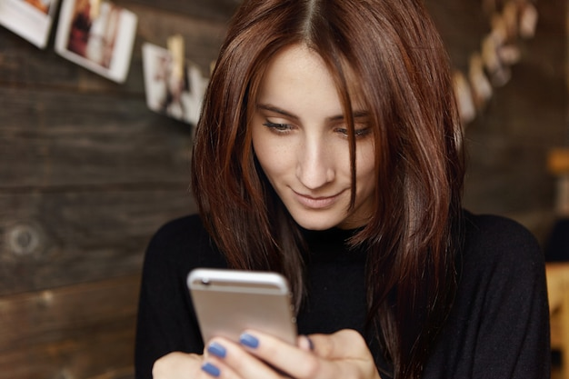 Szybka wiadomość dla przyjaciela. atrakcyjna brunetka europejka za pomocą aplikacji do edycji zdjęć w swoim telefonie komórkowym