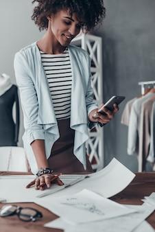 Szybka wiadomość do klienta. piękna młoda afrykańska kobieta patrząca na inteligentny telefon i uśmiechnięta