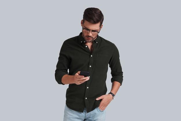 Szybka wiadomość do klienta. przystojny młody mężczyzna w eleganckim stroju casual, trzymający inteligentny telefon i patrzący na niego, stojąc na szarym tle