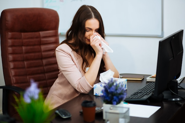 Szybka, zmęczona bizneswoman czuje się wyczerpana, siedząc przy biurku ze zmiętym papierem