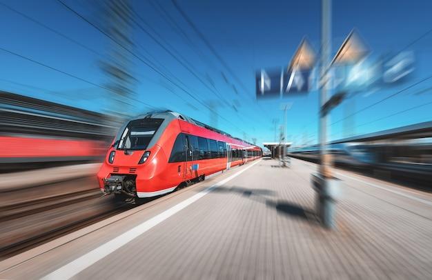 Szybki czerwony pociąg na stacji kolejowej