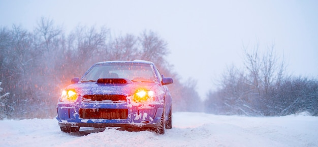 Szybki niebieski samochód sportowy w zimowy śnieżny dzień, zimna pora roku, droga uliczna