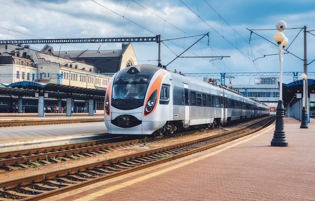 Szybki pociąg na stacji kolejowej na ukrainie. nowoczesny pociąg międzymiastowy na peronie kolejowym. miastowa scena z linią kolejową, budynkami i błękitnym chmurnym niebem.