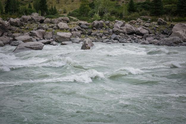 Szybki przepływ wody w górskiej rzece na tle skalistych brzegów, teren do spływu, wysoki stopień trudności.