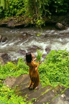 Szybki przepływ. zachwycona młoda kobieta stojąca na schodach i głęboko oddychająca podczas spaceru