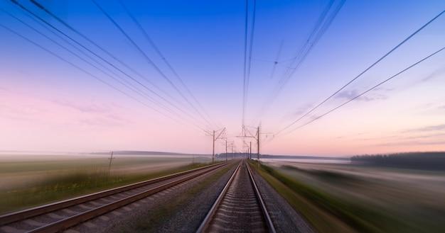 Szybki ruch po linii kolejowej. koncepcja, dostawa koleją, podróż i prędkość. pusta kolej o świcie lub zachodzie słońca.