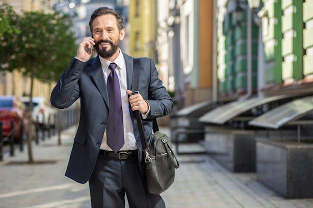Szybki styl życia. wesoły przystojny biznesmen rozmawia przez telefon podczas spaceru do pracy