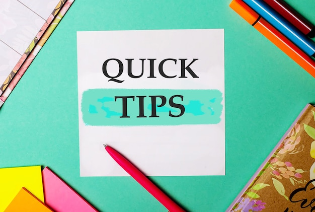Szybkie wskazówki napisane na turkusowym tle w pobliżu jasnych naklejek, notesów i markerów